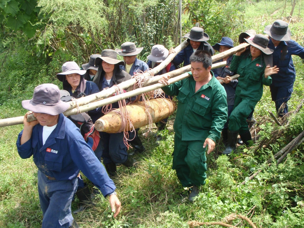 A State Department-funded team of humanitarian deminers carefully removes an unexploded bomb in Laos. Photo courtesy of Mines Advisory Group.