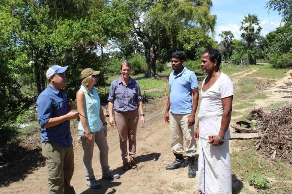 The author (second from left) speaks with the priest at Muhamalai minefield (Photo courtesy of The HALO Trust)