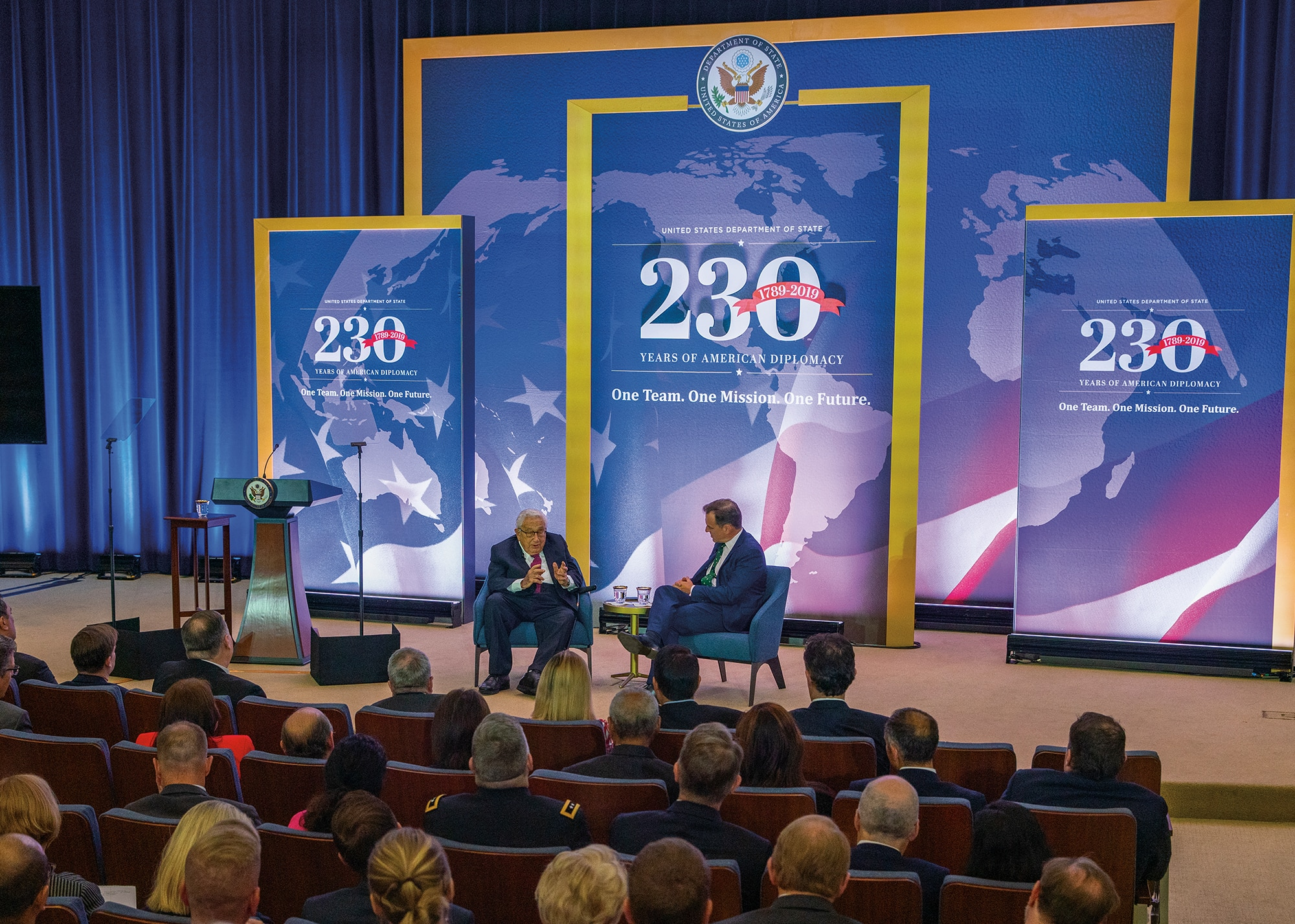 Photo showing former Secretary of State Dr. Henry Kissinger participating in a discussion with his biographer, Dr. Niall Ferguson, at the Department's 230th anniversary celebration in Washington, D.C., July 29, 2019. [Department of State]