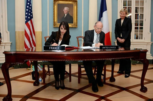 Then-U.S. Special Advisor on Holocaust Issues Stuart Eizenstat and French Human Rights Ambassador Patrizianna Sparacino-Thiellay sign the agreement in Washington, DC, on December 8, 2014.