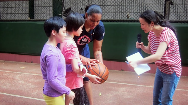 Dr. Andrea Woodson-Smith teaches students in China how to use a basketball.