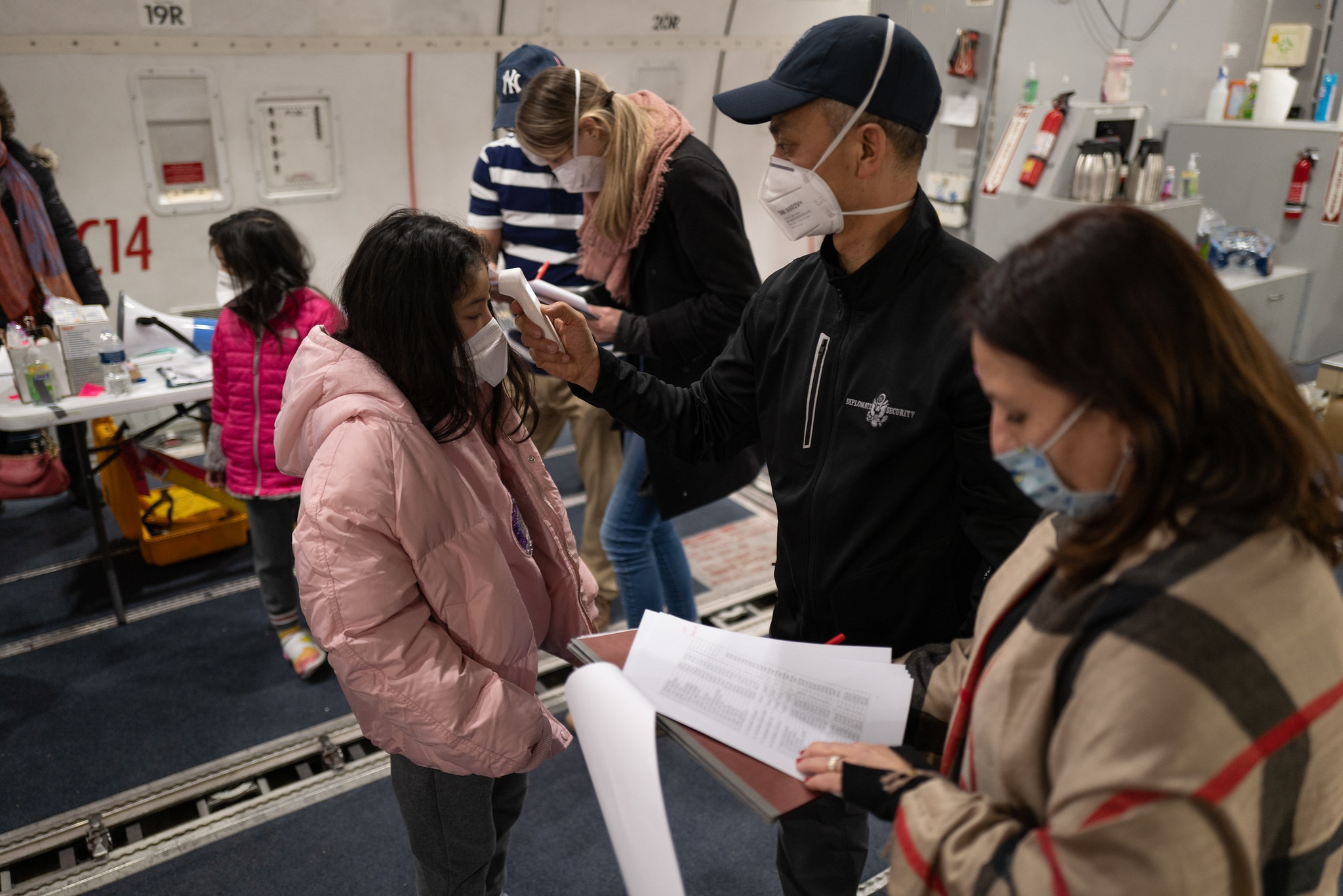 A DSS Regional Security Officer checks a young girl's temperature on the charter flight evacuatingAmerican citizens fromWuhan, China, Jan. 29, 2020. (U.S. Department of State photo)