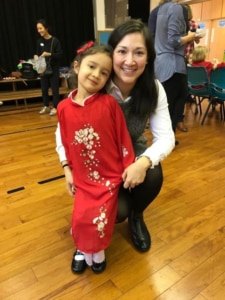 Rachael and her daughter attend a Lunar New Year event where her daughter is wearing a traditional Vietnamese ao dai (Photo courtesy of the Author)