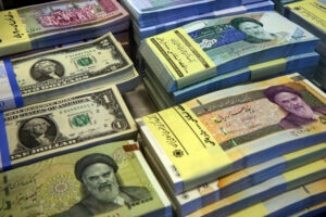In this April 4, 2015 file photo, Iranian and U.S. banknotes are on display at a currency exchange shop in downtown Tehran, Iran. In recent months, Iran has been beset by economic problems despite the promises surrounding the 2015 nuclear deal it struck with world powers.(AP Photo/Vahid Salemi, File)