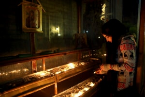 An Iranian Christian woman lights candle at the conclusion of Mass that started on Christmas Eve at the Saint Joseph Chaldean-Assyrian Catholic church in Tehran, Iran, Thursday, Dec. 25, 2014. Iran's minority group of Christians are celebrating Christmas and preparing for the new year. According to official figures, around 120,000 Christians live in Iran, mostly in central and northwestern parts of the country. Iranian Christians represent part of the parliament and freely practice their religion as allowed under the constitution. Other minorities, such as the Jews and Zoroastrians, are recognized in the same way by the law. (AP Photo/Ebrahim Noroozi)