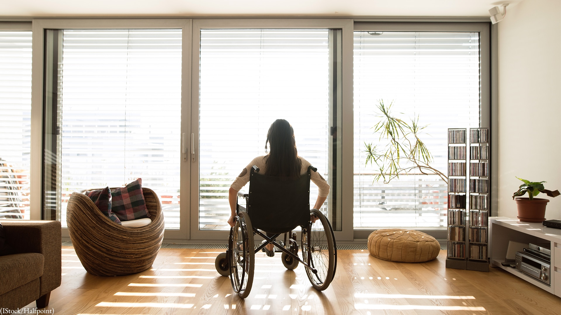 A woman in a wheelchair sits by a bright window.