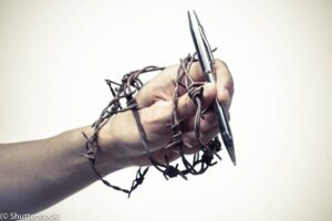 Image of barbed wire wrapped around a hand holding a pen