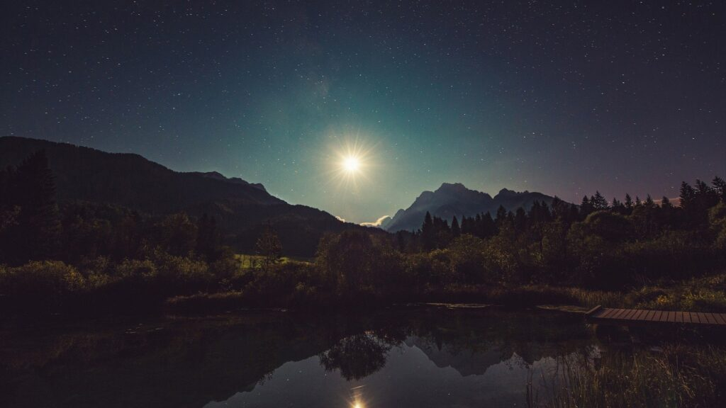 Moon reflecting off lake between two mountains.