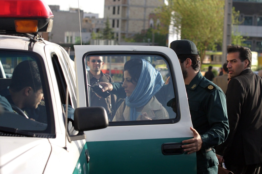 Iranian police officers detain a woman for not adhering to the strict Islamic dress code in Tehran on Saturday April 21, 2007. Police in Tehran arrested women and men failing to confirm to the regime's definition of Islamic morals by wearing loose-fitting hijab, or head scarves, tight jackets and shortened trousers exposing any skin. (AP Photo)