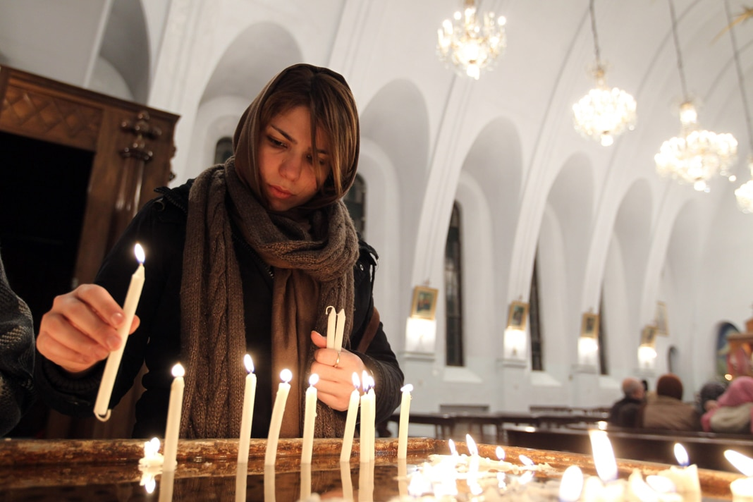 An Iranian Christian woman lights candles during the Christmas Eve mass at the St. Gregor Armenian Catholic church in Tehran on December 24, 2012, as Christians around the world are celebrating Christmas. (Photo credit: ATTA KENARE/AFP via Getty Images)