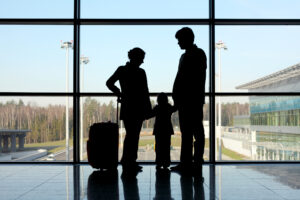 silhouette of mother, father and daughter with luggage standing near window in airport [Shutterstock]