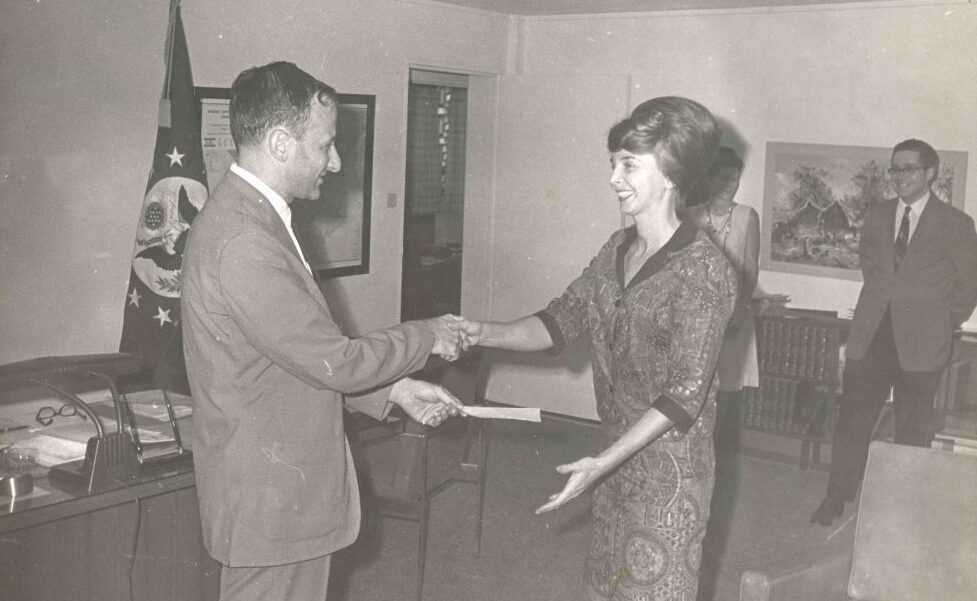 Earlier in her career before becoming a special agent, Patti Morton, pictured right, is presented with a Meritorious Step Increase award by the Chief of Mission in Kinshasa, 1968. (Collection of the National Museum of American Diplomacy)