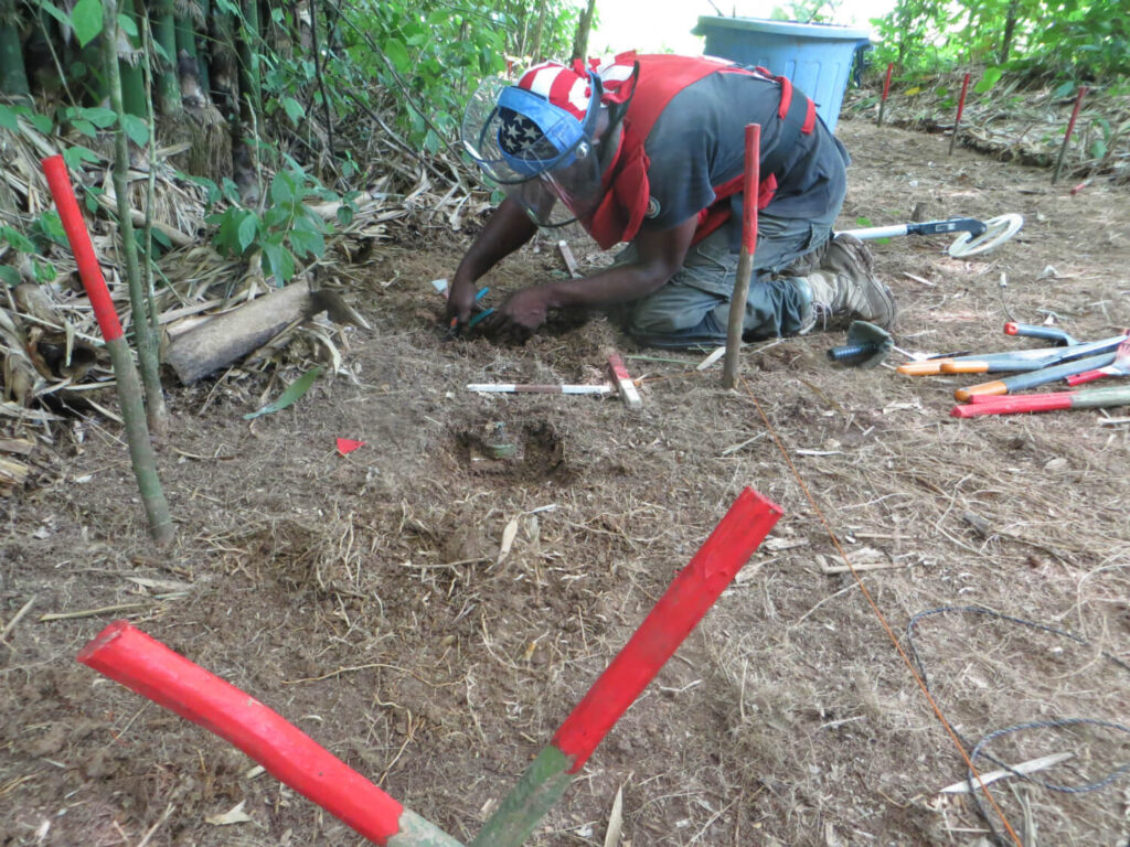 Under a project funded by the United States, a deminer carefully excavates around a landmine. (Photo courtesy DanChurchAid)