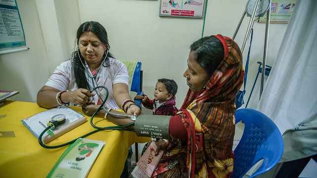 CHITTAGONG, BANGLADESH: February 12, 2017 - Supriya Dae and her son visit paramedic, Shanta Das, for a checkup on his growth. USAID-DFID NGO Health Service Delivery Project supports the delivery of Essential Service Packages (ESP) of primary health care through a network of non-governmental organization (NGO) clinics, commonly known as Smiling Sun Network, that primarily target the poor and under-served focusing more in rural hard-to reach areas and urban slums. This network of service centers incorporates new approaches to promote optimal health behaviors and community participation, and to enhance local ownership of service delivery through institutional strengthening. Photo by Morgana Wingard