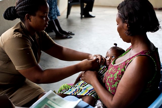 A nurse vaccinates a baby at a clinic in Accra, Ghana. Through its partners and the Ministry of Health, USAID is supporting clinics like this one to improve survival rates of mothers and children. Many countries are facing disruptions to health services amidst COVID-19, and USAID is reminded of the need to protect global immunization progress and continue working towards equitable access to vaccines for all. Photo by Kate Holt, MCSP