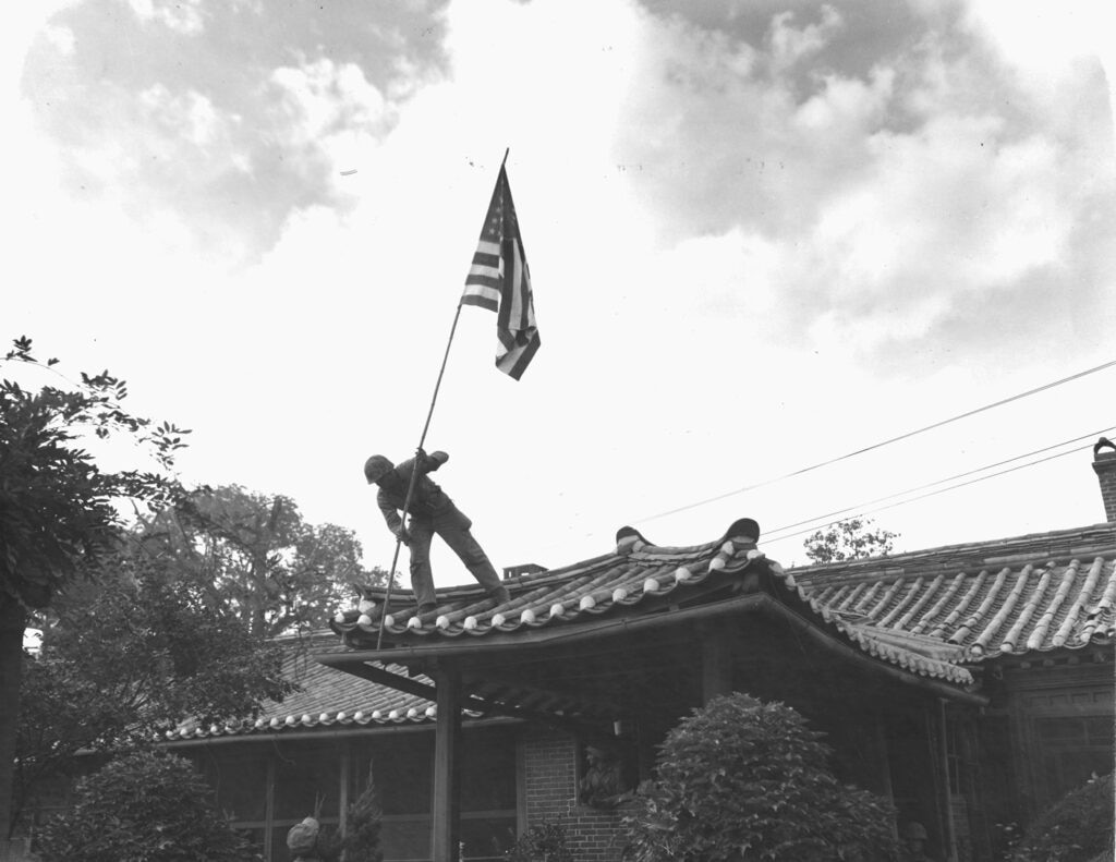 """While fighting for the city raged around the compound, U.S. Marine Corps Pfc. Luther """"Lee"""" Leguire raises the American flag at the U.S. consulate in Seoul, Korea, Sept. 27, 1950. (U.S. Marine Corps photo)"""