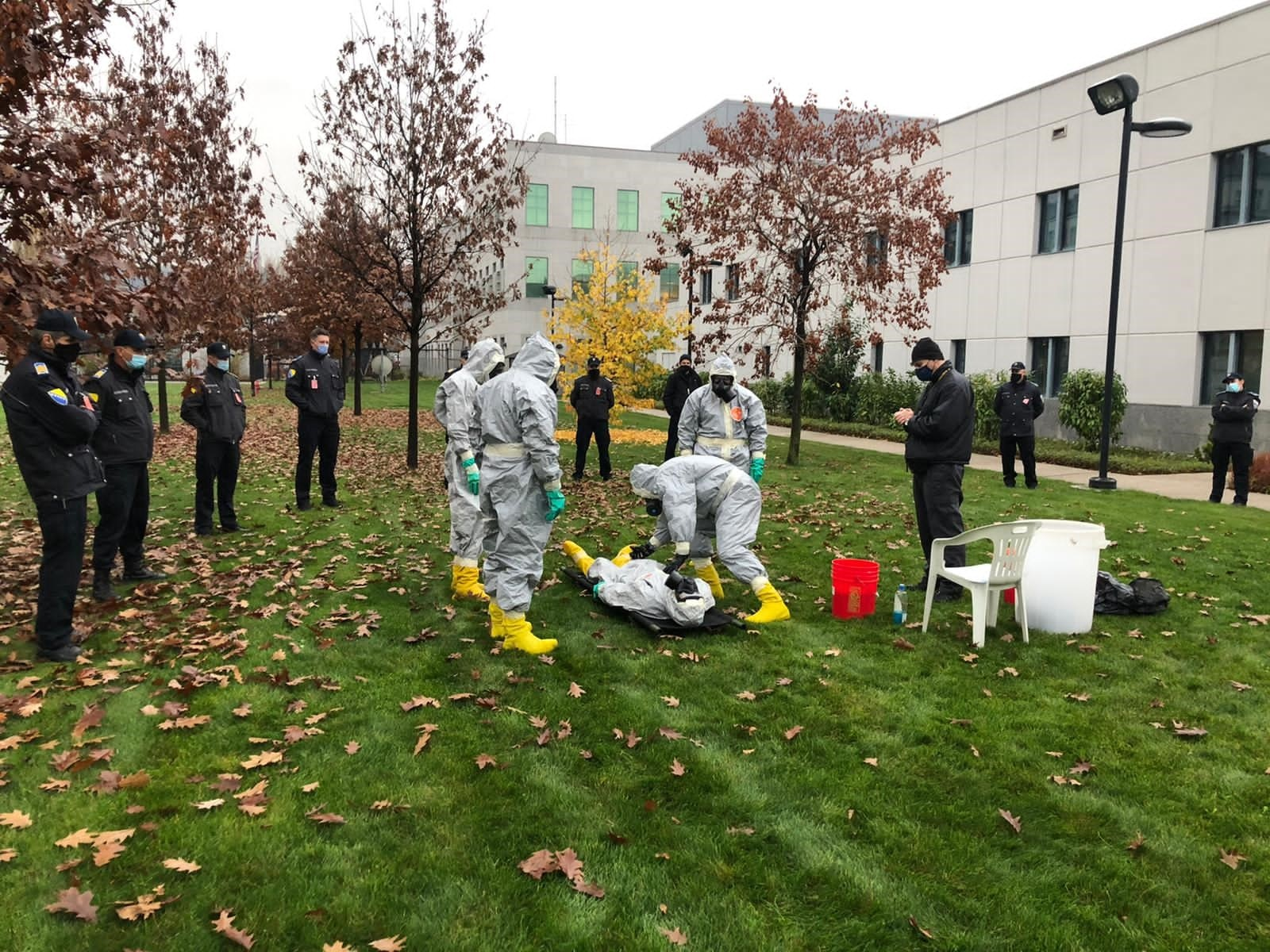 RSO Sarajevo personnel conducts a WMD decontamination exercise to introduce host nation police officers to basic chemical and biological agents. Host nation police officers (standing, left) look on as local guard force WMD first responders conduct a decontamination exercise, U.S. Embassy Sarajevo, November 17, 2020. (U.S. Department of State photo)