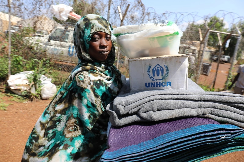 woman carries blankets topped with a box marked with the UNHCR emblem