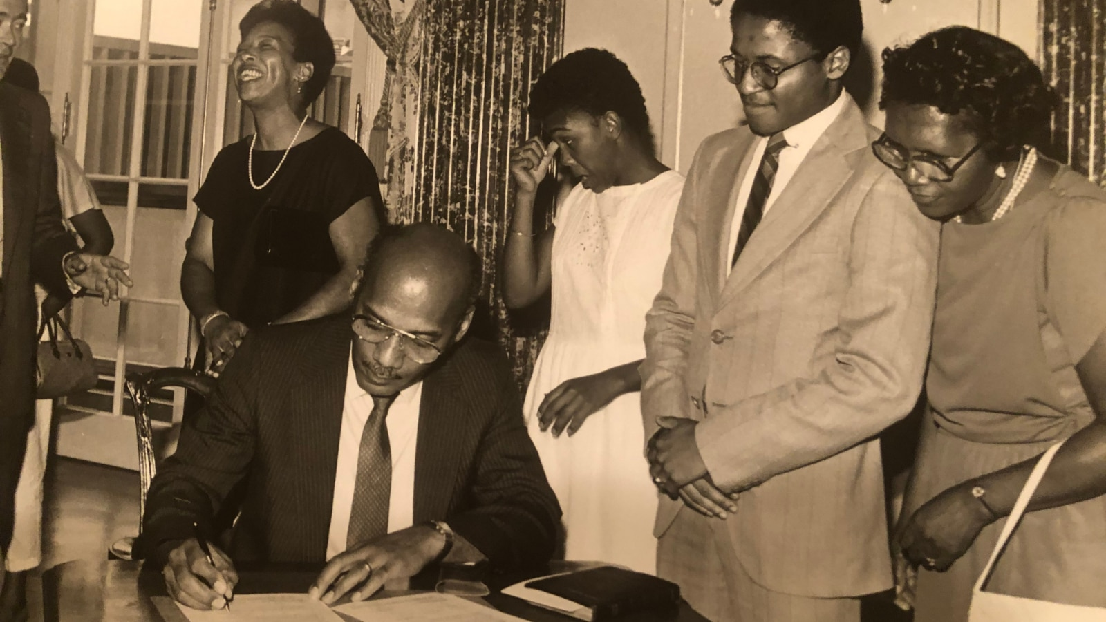 Irv Hicks Jr., along with the Hicks family, witnesses his father, Irvin Hicks, Sr. sign the papers to serve as U.S. Ambassador to Seychelles in 1985. This was Hicks Sr.'s first of three ambassadorships, including the Seychelles, Deputy Representative to the UN, and Ethiopia.
