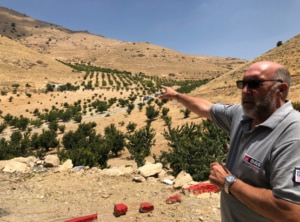 MAG's Technical Field Manager points out an area along the Lebanon-Syria border where local farmers are now able to grow cherries after the area was cleared of landmines and IEDs left by extremists. (State Department photo)