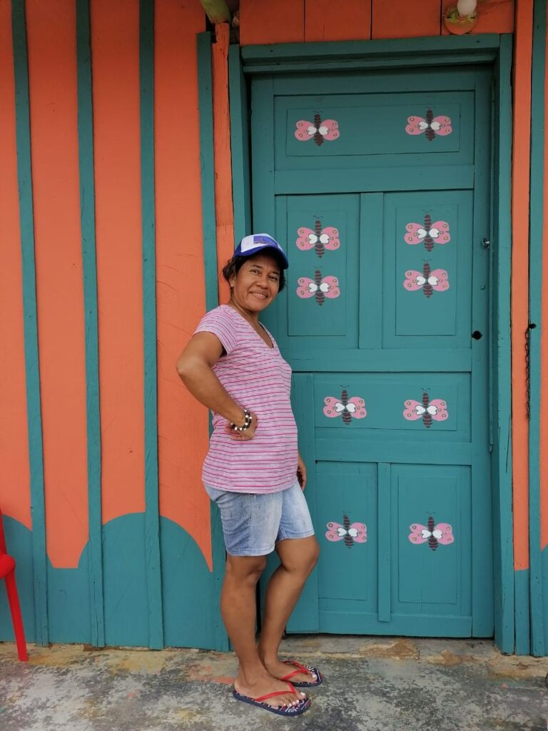 A Colombian woman stands in front of a refurbished home.