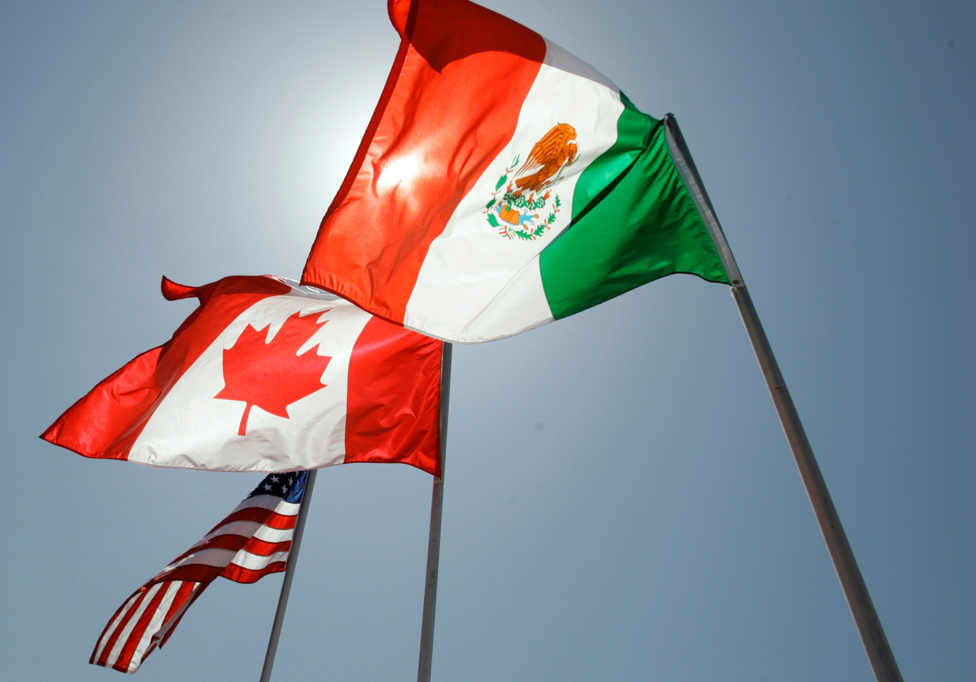 National flags representing the United States, Canada, and Mexico fly in the breeze. (AP Photo/Judi Bottoni, File)