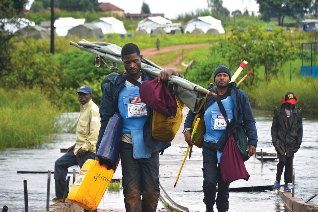 A demining team in Angola traverses a small river with their equipment. [Photo courtesy of HALO]
