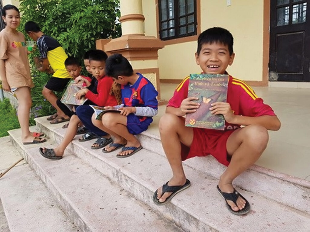 Children in Vietnam look at their new explosive ordnance risk education (EORE) material. Photo courtesy of Golden West Humanitarian Foundation.