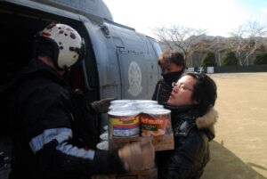 Naval Air Crewman 2nd Class Joseph Conant, from Santee, Calif., gives a Japanese woman canned goods during a humanitarian assistance mission near Sukuiso, Japan on March 18, 2011. [U.S. Navy photo by Mass Communication Specialist 3rd Class Dylan McCord]