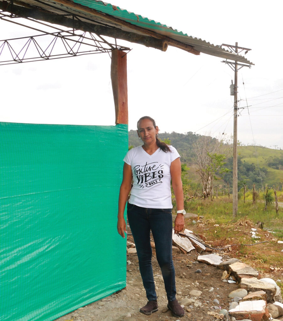 Dory Valazquez stands next to the temporary school. [Story and photo courtesy of HALO]