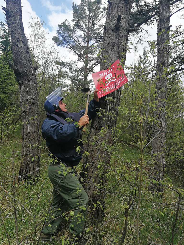A deminer removes the danger mine signs after the completion of the land release activities in one of the locations in East Stari Grad, Sarajevo, Bosnia and Herzegovina. [Photo courtesy of MDDC]