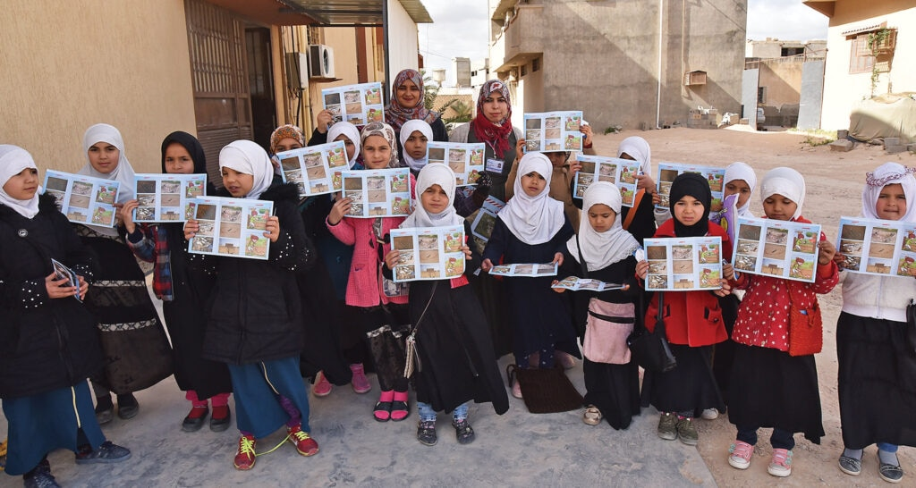 Girls in Libya show their EORE material. [Photo courtesy of HI]
