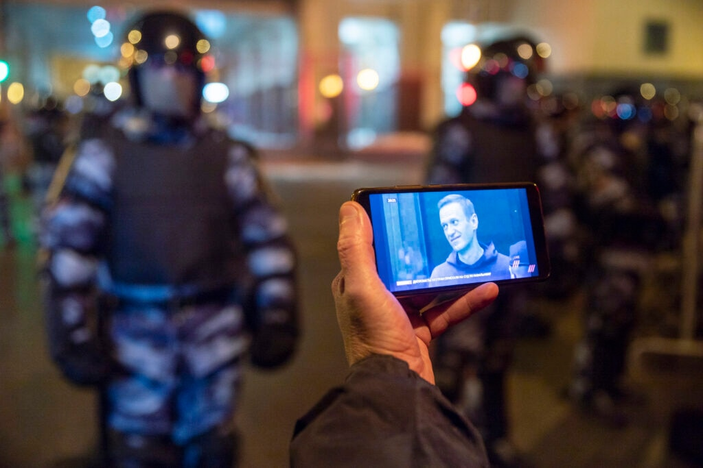 In this file photo taken on Tuesday, Feb. 2, 2021, A journalist watches a live stream of a court hearings with the Russian opposition leader Alexei Navalny on a screen as Russian Rosguardia (National Guard) soldiers guard in front of the court in Moscow, Russia. [AP Image]