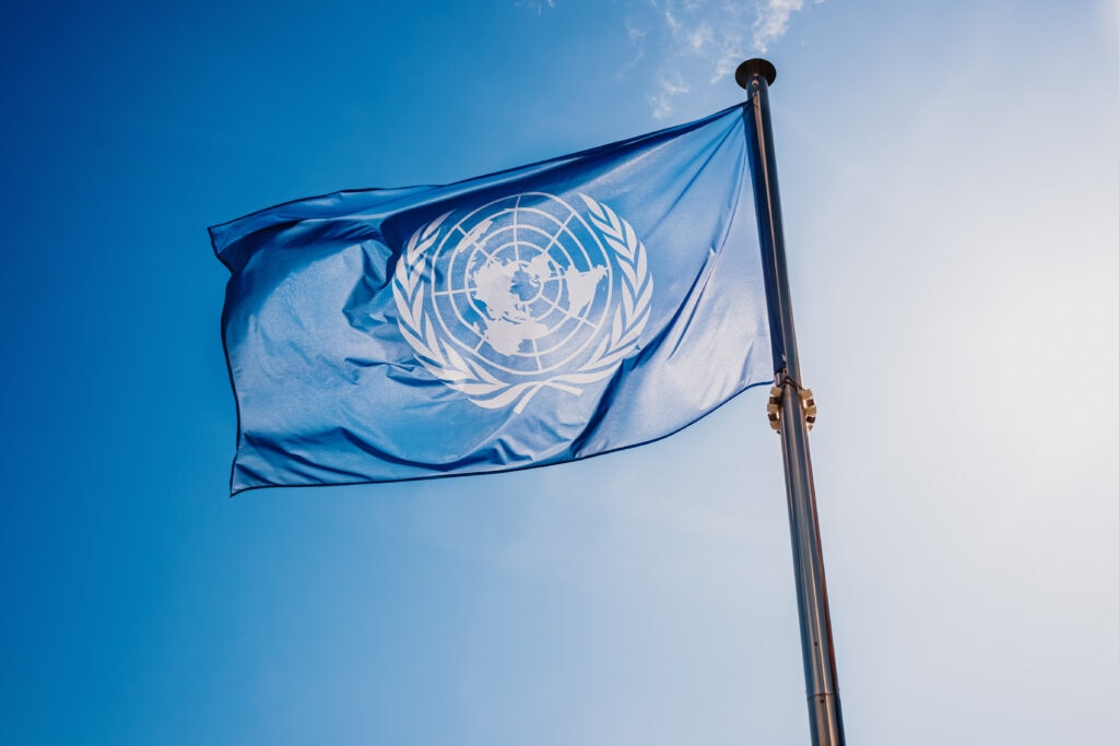 UN flag waved against the sun and blue sky