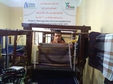 Abdulrahman weaving cloth for sale. (Photo Courtesy of the Marshall Legacy Institute)