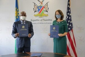 American and Namibian diplomats pose for the camera while wearing masks and standing in front of their respective flags