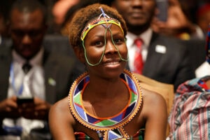 A young Kenyan woman sitting in an audience of smiles