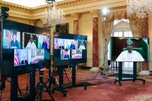 Three large screens set up in elaborate hall containing screen views of leaders at virtual meeting