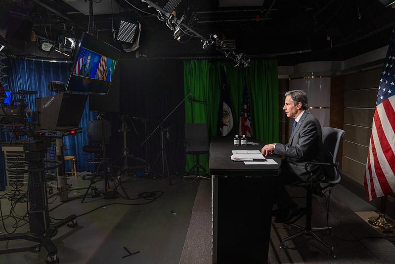 Secretary Blinken sits at a desk speaking to a camera
