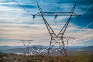 Electrical wires stretching across towers in field
