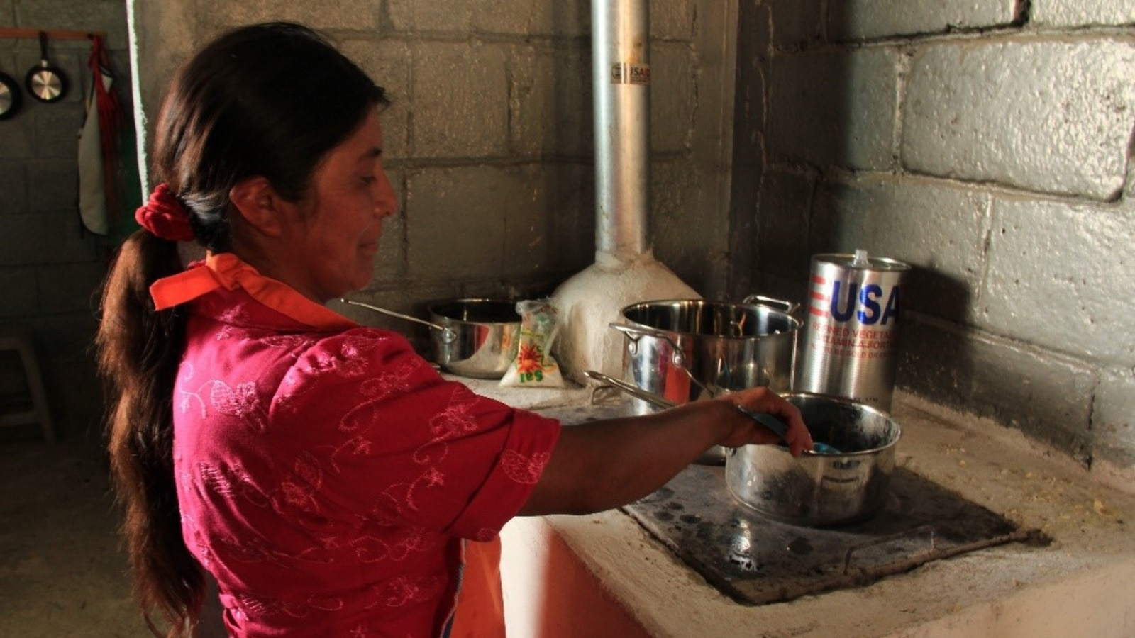 Many women entrepreneurs often operate their businesses out of their homes, pictured here is a Honduran woman working from her kitchen. (Photo courtesy of USAID)