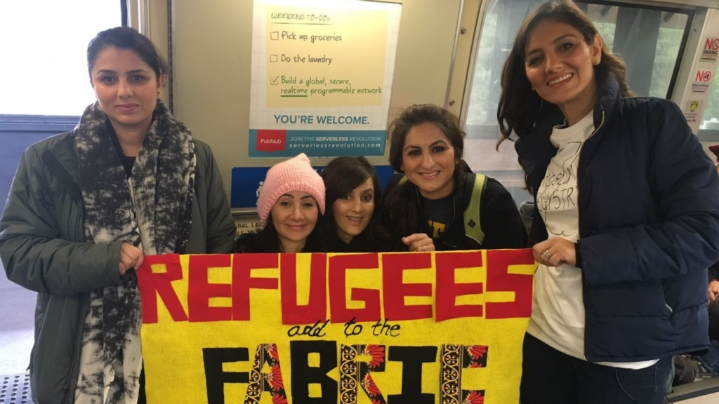 """This photo of Nabila and her sisters was taken on Inauguration Day, January 21, 2017. Nabila is the one in the pink hat. She and her four sisters hold a sign that says, """"Refugees add to the fabric."""" (Photo courtesy of Nabila)"""
