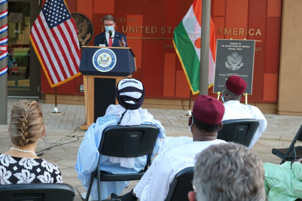 Ambassador Eric Paul delivers a speech from a podium to a small audience in front of the country flags for the United States and Niger