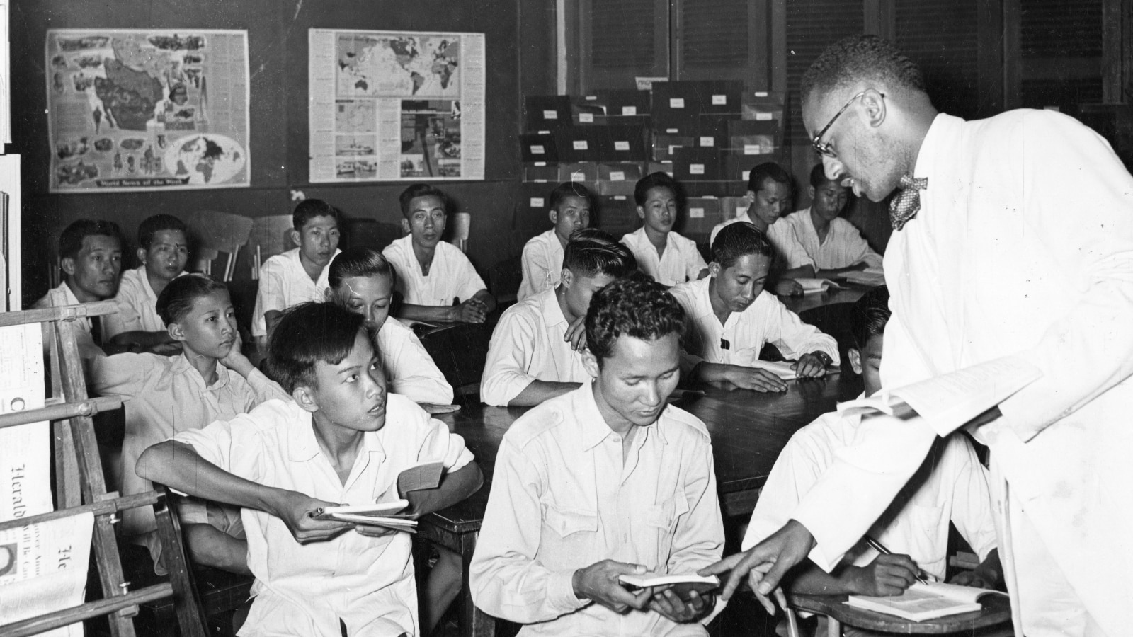 In the early years of the Fulbright Program in Cambodia, U.S. Fulbrighter Charles R. Sadler (right) teaches English to students in Phnom Penh from Ecole Descartes, Lycee Sisowath, Ecole Miche, and members of the city's Police Department. (Photo courtesy of University of Arkansas Libraries Special Collections/ Public Domain)