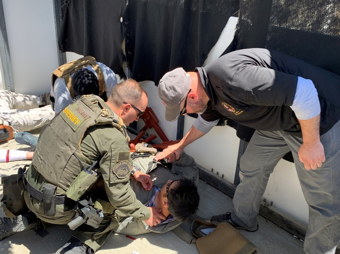 A Diplomatic Security Service (DSS) special agent (back left) and a Contra Costa County Sheriff SWAT operator (left foreground) provide medical care under the guidance of a DSS operational medicine instructor (far right), Clayton, Calif. May 2021, (U.S. Department of State photo)