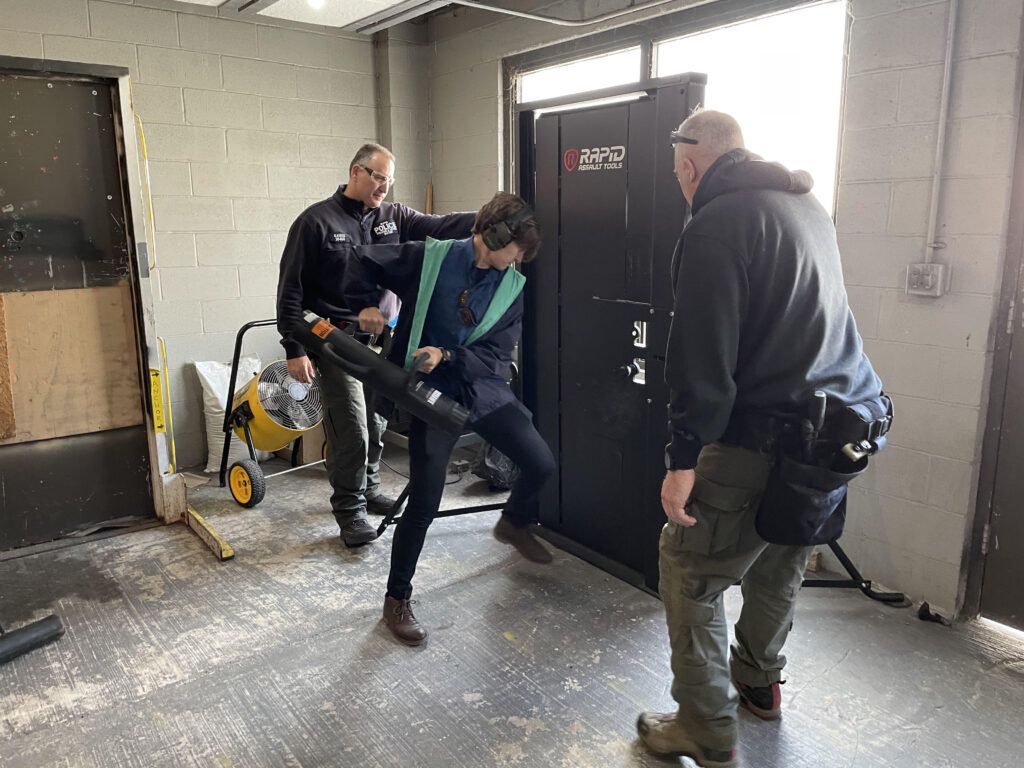 New York City Police Department (NYPD) Advanced Tactics Unit instructors, Police Officer John Kaiser and Detective Liam Swords, at the New York National High Intensity Drug Trafficking Area (HIDTA) Training Center, flank a DSS special agent as she practices door breaching techniques, April 29-30, 2021. (U.S. Department of State photo)