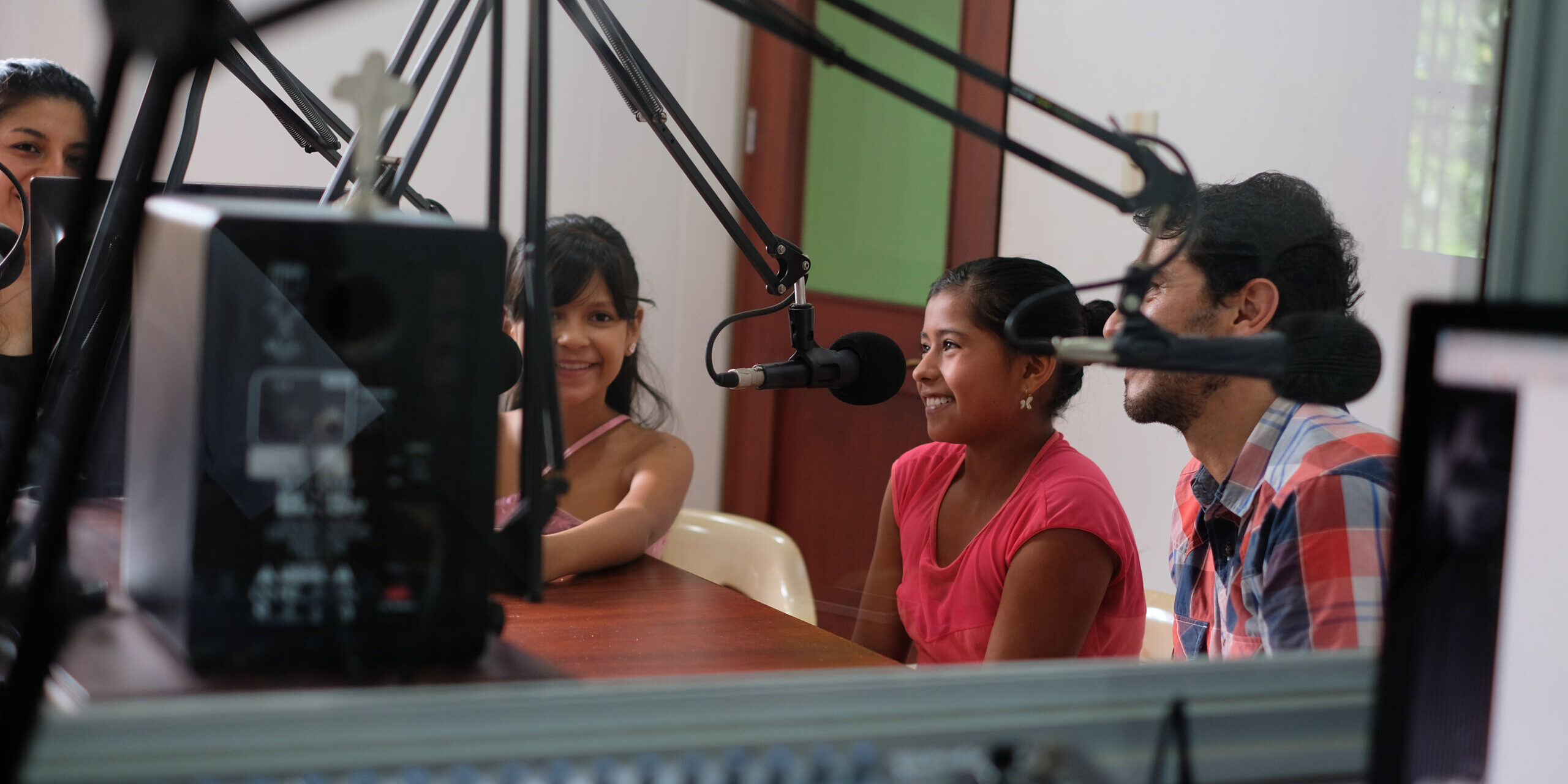 Four people including two children speaking into microphones around a table.