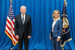 President Biden and Doreen pose for a picture in front of the United States and presidential flags.
